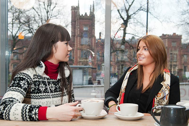 two female students drinking coffee in the students union with the Lanyon building in the background